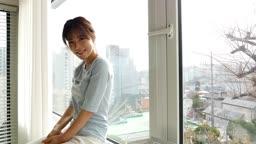 라이프스타일 집에서 창가에 앉아 카메라 응시하며 미소짓는 젊은여자 모습