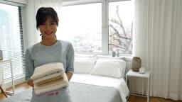 라이프스타일 집 침대에서 세탁이 완료된 수건을 들고 카메라 응시하며 미소짓는 젊은여자 모습