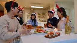 라이프스타일 거실 테이블에서 술잔 들고 건배하며 카메라 응시하는 친구들 모습