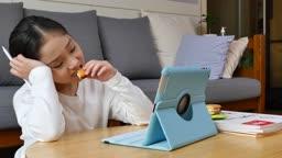 홈스쿨링 과자를 먹으면서 태블릿피씨 보며 힘들어하는 초등학생 모습
