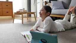 홈스쿨링 거실에 누워 공부하며 미소짓는 초등학생 모습