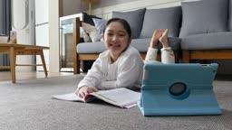 홈스쿨링 거실에 누워 카메라 응시하며 미소짓는 초등학생 모습