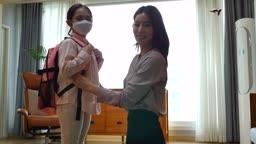 워킹맘 거실에서 출근전 마스크 착용하고 카메라 응시하며 미소짓는 엄마와 딸 모습
