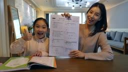 워킹맘 식탁에 앉아 시험지를 보며 자랑하는 엄마와 딸 모습