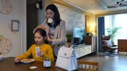워킹맘 식탁에 앉아 출근전 머리를 정리해주는 엄마와 아침을 먹는 딸의 모습