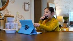 라이프스타일 식탁에 앉아 혼자 삼각김밥을 먹으며 태블릿피씨를 조작하는 초등학생 모습