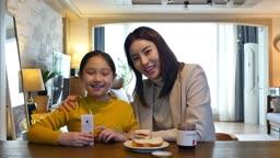 워킹맘 식탁에서 아침 밥 먹으며 카메라 응시하며 미소짓는 엄마와 딸 모습