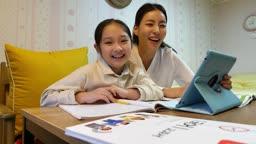 워킹맘 퇴근후 재미있게 공부하며 카메라 응시하며 미소짓는 엄마와 딸 모습