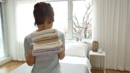 라이프스타일 집 침대에서 세탁이 완료된 수건의 향을 맡는 젊은여자 모습