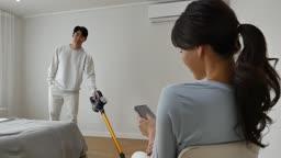 라이프스타일 집 침대에서 스마트폰 조작하는 젊은여자와 청소기로 청소하는 젊은남자 모습