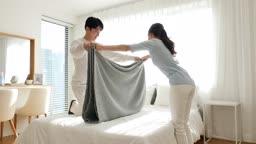 라이프스타일 집 침대에서 이불을 정리하는 커플 모습