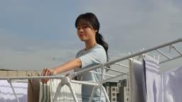라이프스타일 집 옥상에서 건조대에 세탁물을 정리하고 휴식을 취하는 젊은여자 모습