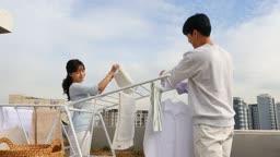 라이프스타일 집 옥상에서 건조대에 세탁물을 정리하는 커플 모습