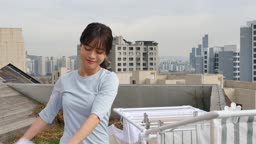 라이프스타일 집 옥상에서 건조대에 세탁물을 정리하는 젊은여자 모습
