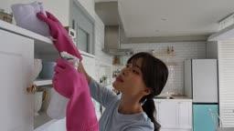 라이프스타일 주방에서 고무장갑 끼고 분무기 뿌리며 청소하는 젊은여자 모습
