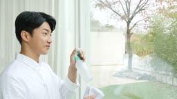 라이프스타일 거실 창가에서 분무기와 수건으로 창 닦는 젊은남자 모습