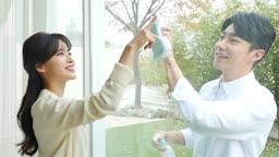 라이프스타일 거실 창가에서 분무기와 수건으로 창 닦는 커플 모습