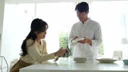 라이프스타일 주방에서 수건으로 그릇 정리하는 커플 모습