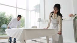 라이프스타일 거실 테이블에 테이블보 정리하는 커플 모습