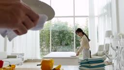 라이프스타일 거실 테이블에 그릇을 놓는 젊은여자와 그릇을 닦는 젊은남자 손 모습