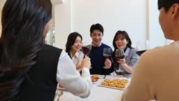 홈파티 거실 테이블에 앉아 와인잔 들고 건배하는 친구들 모습