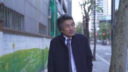 거리에서 외로이 걷는 중년 비즈니스맨 모습