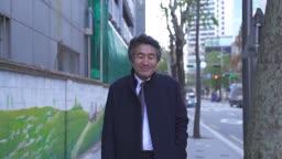 거리에서 미소 지으며 걷는 중년 비즈니스맨 모습