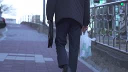 퇴직 외로이 술이 든 비닐봉지와 가방을 들고 거리를 걷는 중년 비즈니스맨 뒷 모습