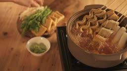 겨울음식 끓는 육수에 어묵탕 음식 재료들 넣는 손 모습