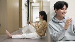 스마트홈 비즈니스 재택근무 집 복도에 앉아서 태블릿피씨하는 젊은여자와 젊은남자 모습