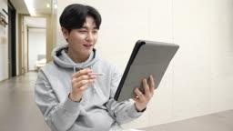스마트홈 비즈니스 재택근무 집 복도에 앉아서 태블릿피씨하는 젊은남자 모습