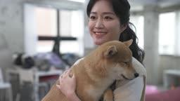 애견카페 강아지를 안고 미소짓는 직원 모습