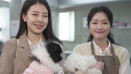 애견카페 강아지를 안고 카메라 응시하며 미소짓는 견주 젊은여자와 직원 모습