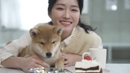 애견카페 강아지와 함께 카메라 응시하며 미소짓는 견주 젊은여자 모습