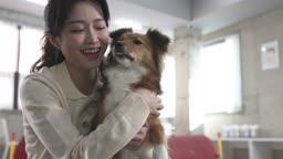 애견카페 강아지를 안고 카메라 응시하며 미소짓는 견주 젊은여자 모습