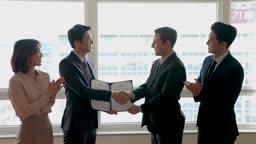 비즈니스 외국 바이어와 MOU 체결 후 악수하는 비즈니스맨과 박수치는 직원들 모습
