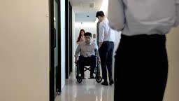 비즈니스 휠체어를 탄 비즈니스맨과 복도를 통행하는 직원들 모습