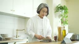 실버서퍼세대 마늘 썰며 태블릿으로 요리 레시피 보는 노년층여자 모습