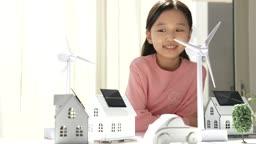 미래의 어린이 태양열 집 모형과 태양열 풍력발전기 모형 쳐다보는 초등학생 모습