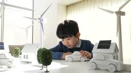 미래의 어린이 태양열판을 집 모형에 붙이는 초등학생 모습