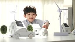 미래의 어린이 자동차와 태양열 집과 풍력발전기 모형들 만지는 초등학생 모습