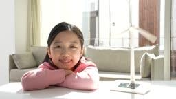 미래의 어린이 풍력발전기 모형과 웃는 초등학생 모습