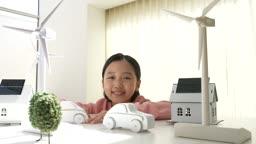 미래의 어린이 태양열 집 모형과 태양열 풍력발전기 모형 앞에서 웃는 초등학생 모습