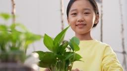 미래의 어린이 화분에 담긴 식물과 웃는 초등학생 모습
