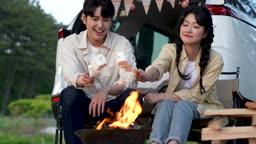 차박캠핑 화로대 불에 마시멜로우 굽는 젊은남자와 젊은여자 모습