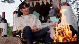 차박캠핑 의자에 앉아 화로대 불을 쳐다보며 불멍하는 젊은남자 모습
