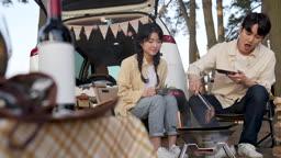 차박캠핑 그리들에 고기 굽는 젊은남자와 젊은여자 모습
