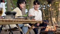차박캠핑 화로대 불에 새우 굽는 젊은남자와 젊은여자 모습