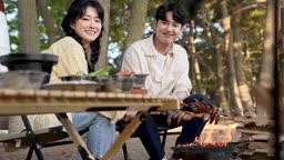 차박캠핑 화로대 불에 새우 구우며 웃는 젊은남자와 젊은여자 모습