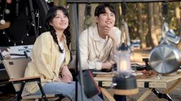 차박캠핑 의자에 앉아 풍경 바라보는 젊은남자와 젊은여자 모습
